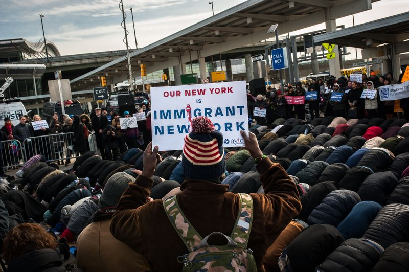 Muslim men pray while supporters hold up signs during a rally at John F. Kennedy Airport on Feb. 3.
